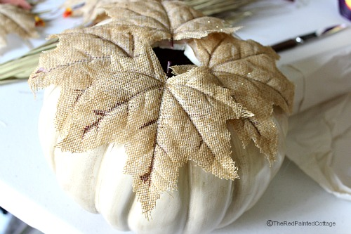 Gluing burlap leaves on pumpkins before stacking.